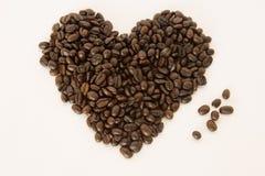 咖啡豆在白色背景的心脏形状安排了 库存照片