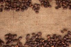 咖啡豆在粗麻布分散 免版税库存图片
