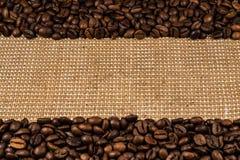 咖啡豆在粗麻布分散 免版税库存照片