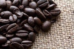 咖啡豆在粗麻布背景放下 库存照片