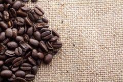 咖啡豆在粗麻布背景,关闭放下  库存图片