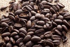 咖啡豆在粗麻布背景,关闭放下  库存照片