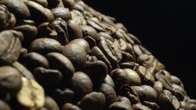 咖啡豆在自转特写镜头黑色背景中 股票视频