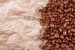 咖啡豆在被击碎的纸背景的 图库摄影