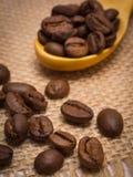咖啡豆堆与木匙子的在黄麻帆布 免版税库存图片