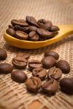 咖啡豆堆与木匙子的在黄麻帆布 库存图片