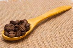 咖啡豆堆与木匙子的在黄麻帆布 库存照片