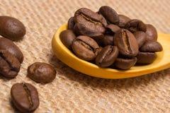 咖啡豆堆与木匙子的在黄麻帆布 免版税库存照片