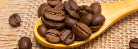 咖啡豆堆与木匙子的在黄麻帆布 免版税图库摄影