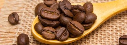 咖啡豆堆与木匙子的在黄麻帆布 图库摄影