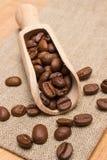 咖啡豆堆与木瓢的在桌上的黄麻粗麻布 图库摄影