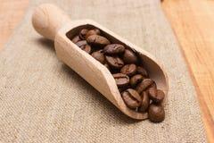 咖啡豆堆与木瓢的在桌上的黄麻粗麻布 免版税库存图片