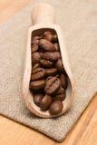 咖啡豆堆与木瓢的在黄麻粗麻布 免版税库存图片
