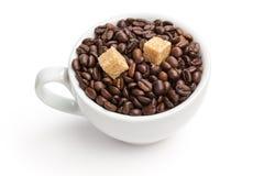 咖啡豆堆在杯子的用蔗糖 库存图片