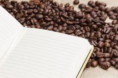 咖啡豆堆在粗麻布和记事本的 免版税库存照片