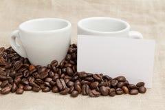 咖啡豆堆在粗麻布的与二个杯子 库存图片