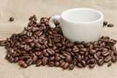 咖啡豆堆在粗麻布的与杯子 免版税图库摄影
