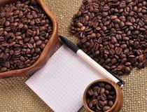 咖啡豆堆在粗麻布和笔记薄背景的 库存图片