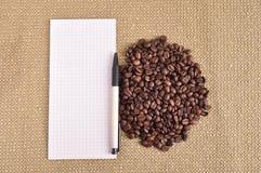 咖啡豆堆在粗麻布和笔记薄背景的 免版税图库摄影