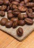 咖啡豆堆在黄麻粗麻布的在桌上 免版税图库摄影