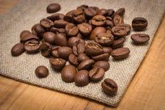 咖啡豆堆在黄麻粗麻布的在桌上 库存图片
