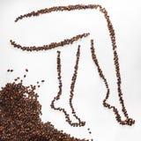 咖啡豆弯曲的妇女脚剪影在白色背景隔绝的 概念减重和美好的图 库存图片