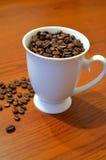 咖啡豆涌入了一个白色杯子 库存照片