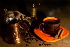 咖啡豆溢出了在袋子、磨咖啡器、咖啡罐、在昏暗的光的咖啡和桂香外面 免版税库存图片