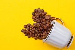 咖啡豆溢出在杯子外面 免版税图库摄影