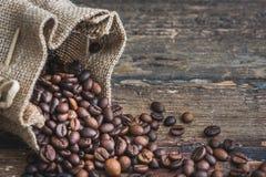 咖啡豆溢出在粗麻布大袋外面 免版税库存照片