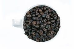 咖啡豆溢出杯子顶视图 图库摄影