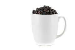 咖啡豆溢出杯子 免版税库存照片