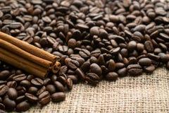 咖啡豆用在粗麻布背景的肉桂条与空的空间的文本的 免版税库存图片