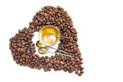 咖啡豆的心脏和antuque杯子和匙子在白色背景 库存照片