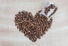 从咖啡豆的心脏在木背景 库存照片