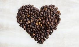 从咖啡豆的心脏在木背景 库存图片