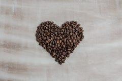 从咖啡豆的心脏在木背景 免版税库存图片