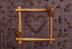 咖啡豆的重点在肉桂条框架的 免版税库存照片