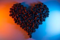 咖啡豆突出与氖被排行以心脏的形式 库存照片