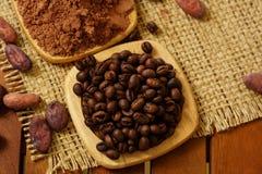 咖啡豆,可可粉,在粗麻布的木板材 图库摄影