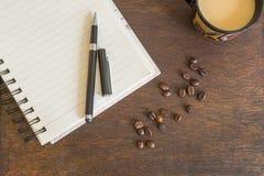 咖啡豆,咖啡,在木甲板的笔记本 免版税库存图片