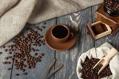 咖啡豆,碾碎的咖啡和热的饮料在一杯,木表面上 图库摄影