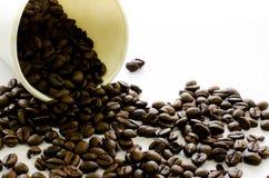 咖啡豆从在白色背景的白皮书杯子流动 免版税库存照片