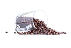 咖啡豆从在白色backgrou隔绝的一个玻璃杯子溢出 库存图片