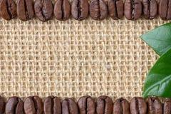 咖啡边界 豆和叶子在粗麻布背景 免版税库存图片