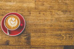 咖啡顶视图在红色杯子的在木桌背景 库存照片