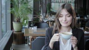 咖啡饮用的妇女年轻人 女性举行的杯子 写博克的女孩,浏览互联网,聊天 股票录像