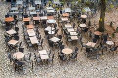 从咖啡馆上室外空的桌和椅子的看法  免版税库存图片
