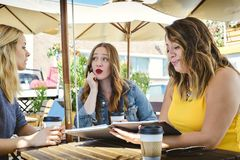 咖啡馆与3位年轻专家的业务会议 免版税库存图片