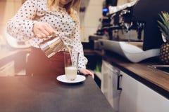 咖啡馆倒热的发泡的牛奶的雇员barista对玻璃 图库摄影